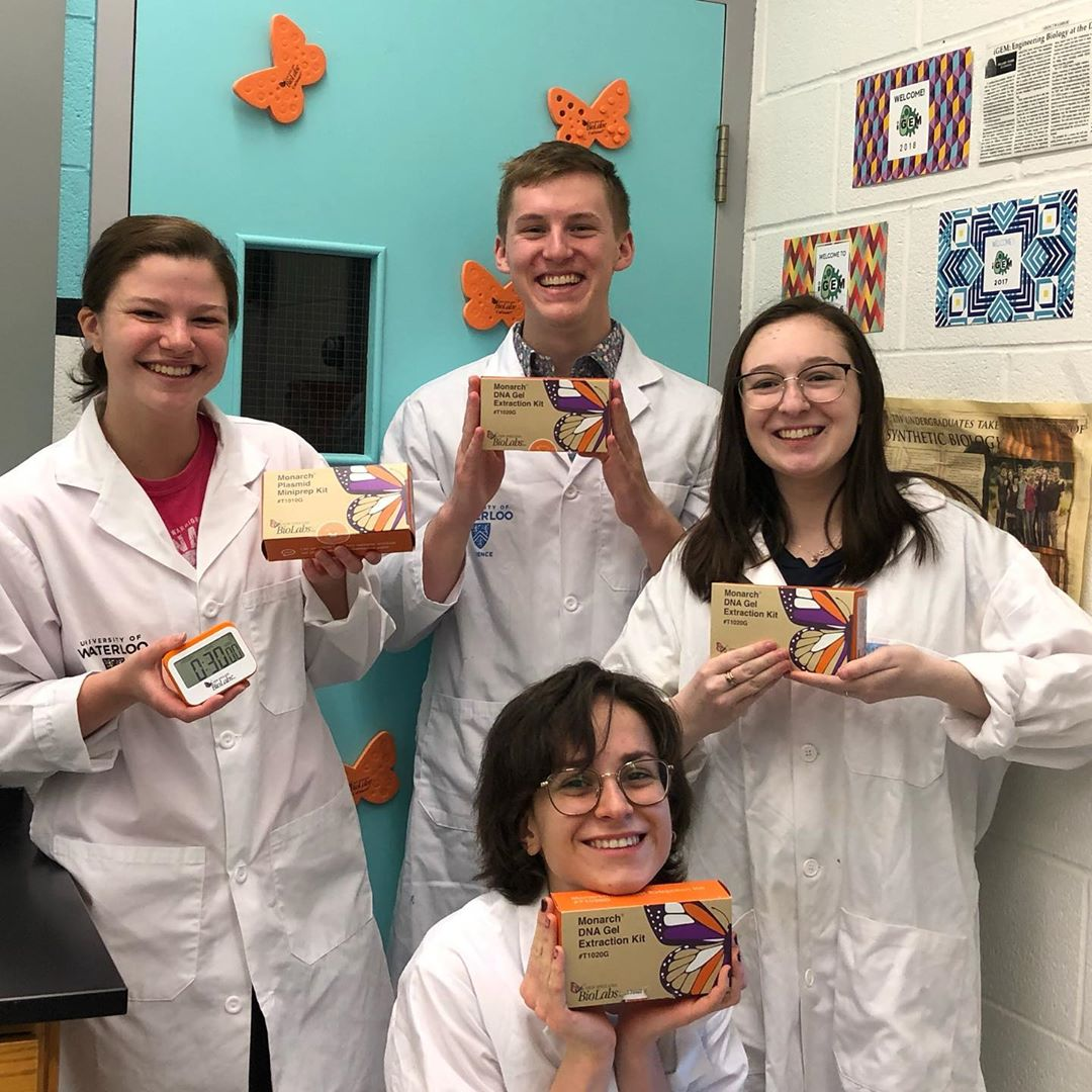 Waterloo iGem team holds up Monarch DNA extraction gel kit.