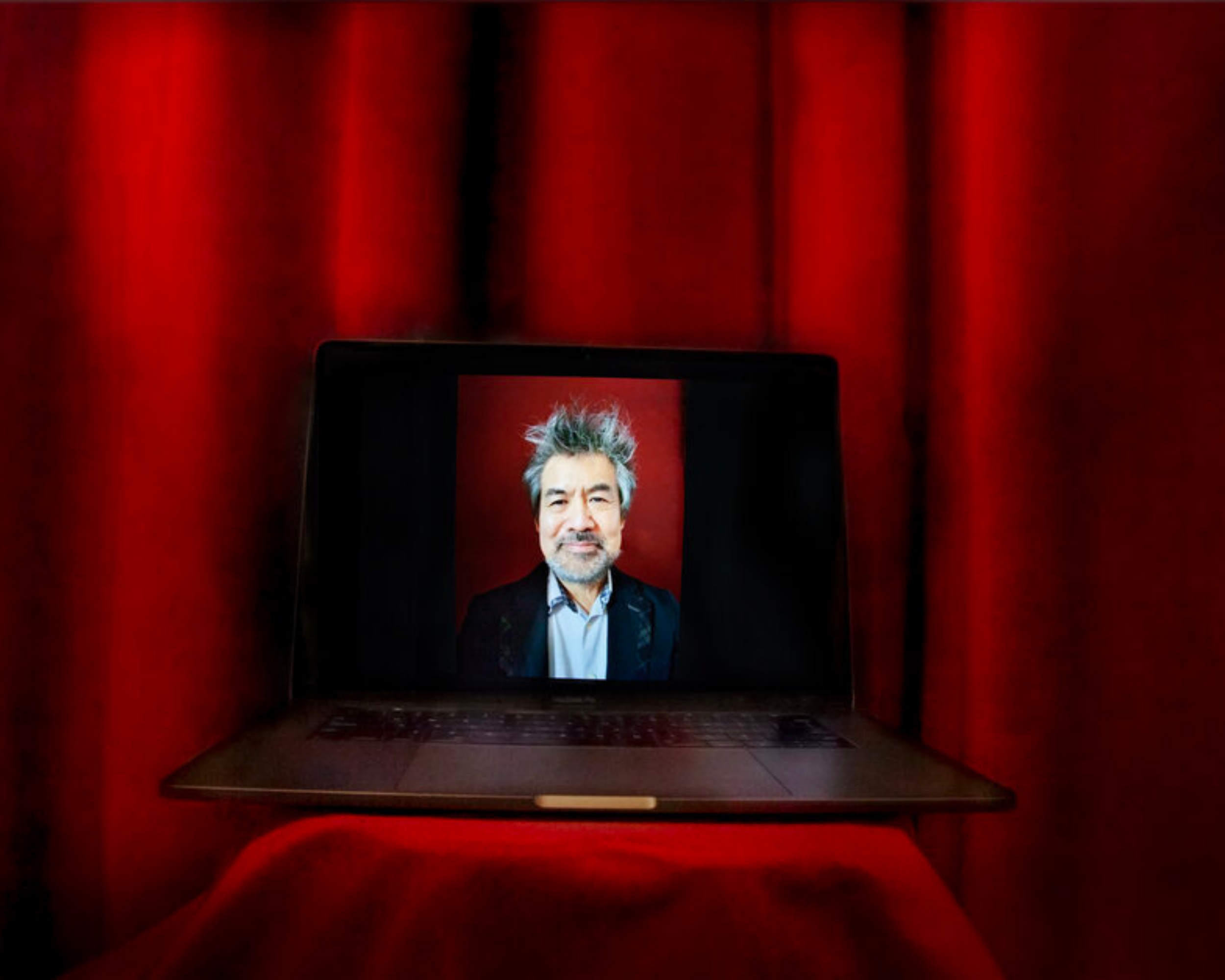 An image of a man in a suit jacket is displayed on a laptop screen with a red curtain background. The laptop in on a red table.