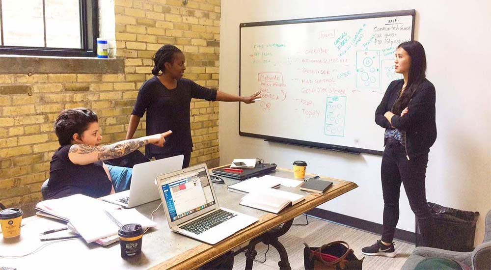 Group of 3 students working together at a whiteboard, with computers on table.