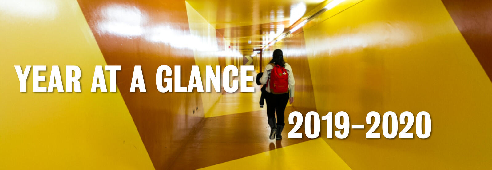 A student walking down the tunnel wearing a red backpack with the words Year ta  Glance 2019 - 2020.