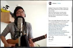 A screenshot from Lyle Kam's Instagram, he wears headphones and stands in front of a microphone with his guitar, sinnging. There is a plush goose behind him, in a yellow hardhat