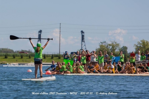 Madeline holding paddle in front of On Board participants