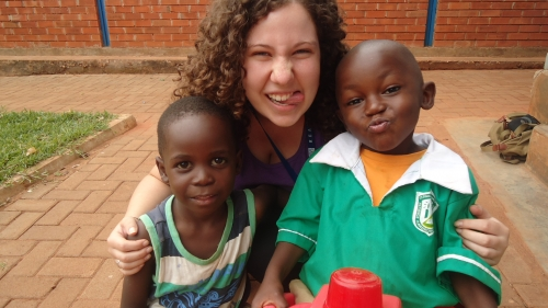 Jenna Bott poses with two children she worked with in Uganda.