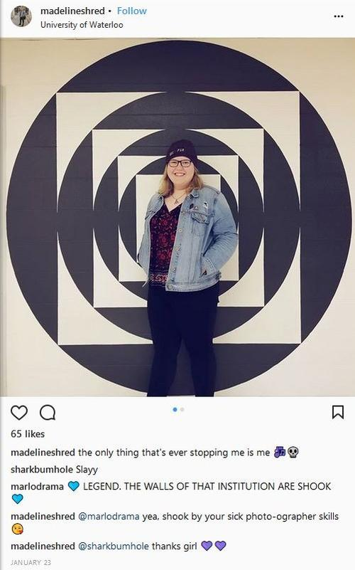 A student standing in front of a geometric wall painting