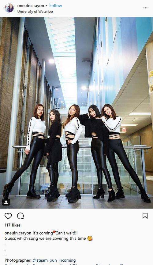A shot of 5 girls at a low angle wearing white and black, posed