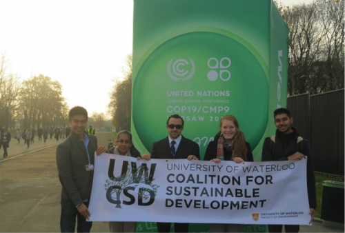 "Waterloo delegates pose in Poland with a ""University of Waterloo Coalition for Sustainable Development"" banner."