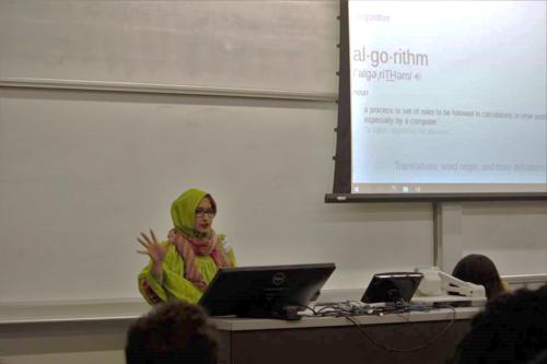 Fatema presents next ot a presentation slide that defines an algorithm
