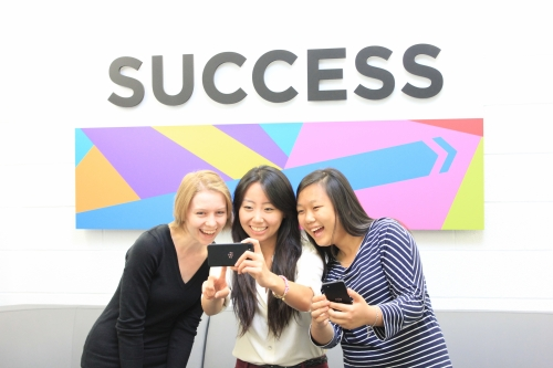 Anastasia Santasheva, Dinah Shi, and Cheyenne Guo play with their BlackBerry phones in the Student Success Office.