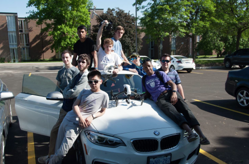 Jordan and his production team posing in front of a car