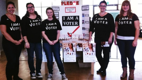 Renison group standing beside their I Am A Voter booth