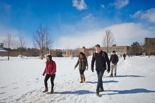 Students walking across BMH green in the winter time