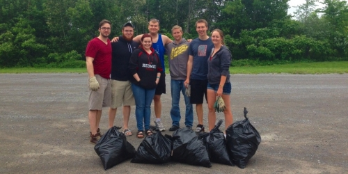 Phil and his volunteers stand together behind bags of trash they cleaned up in Arnprior.