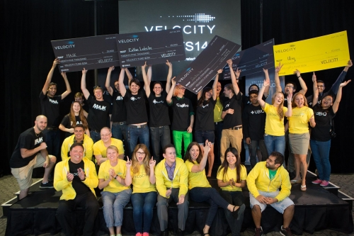 Velocity Fund Finals winners hold up their giant cheques on stage.
