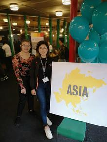 "Jenny Koo and Erika Tan beside a sign that says ""Asia""."