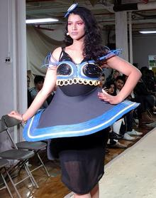 "Student modelling a dress made from e-waste cables for the ""Waste"" segment."