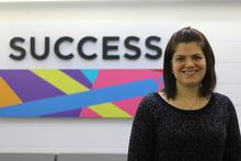 "Laura Stickel beside ""Success"" sign"