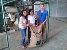 Wil Schmor and two colleagues pose with a sack of coffee beans.