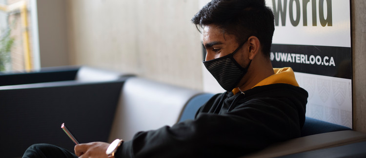 student with face mask sitting and looking at mobile phone