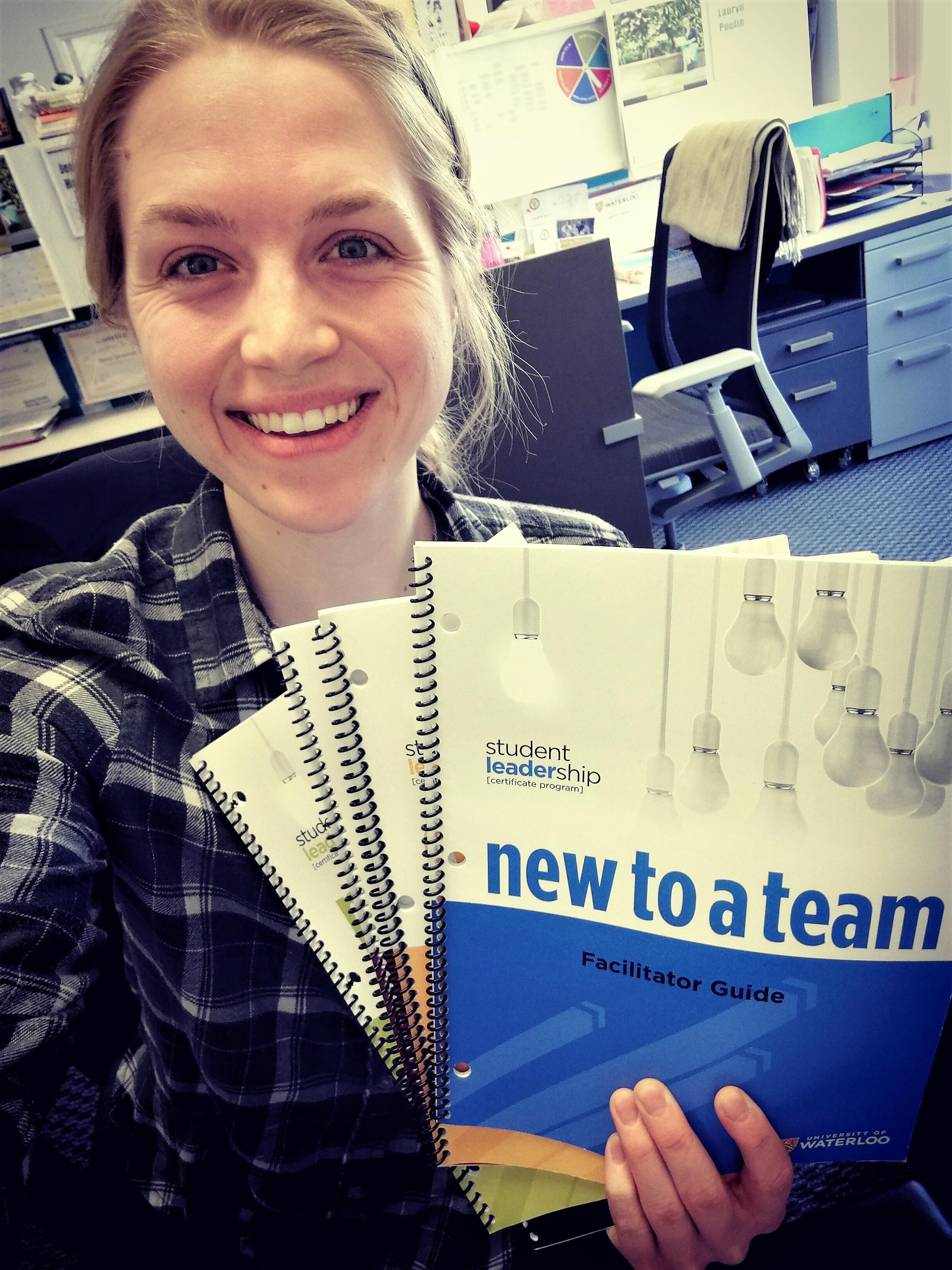 Emma, our coop student, holding Stundent Leadership Program Booklets