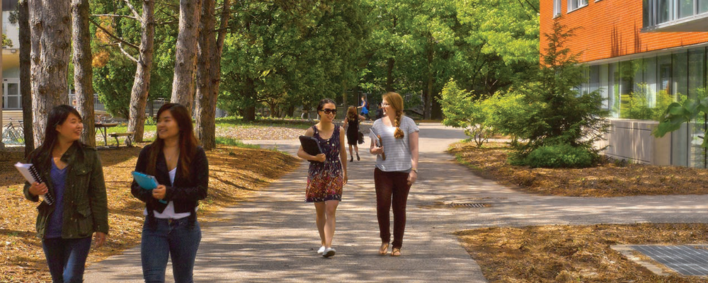 Students walking on campus by the Tatham Centre