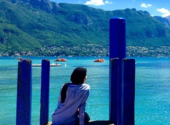 A student sitting at the end of a dock in the south of France.