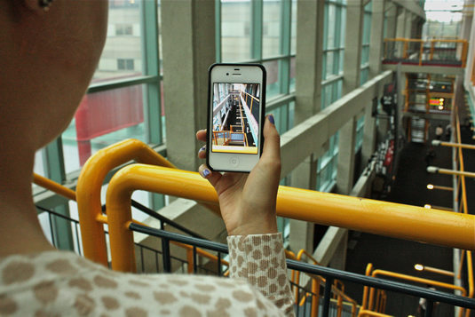 Student taking a photo with her iPhone in the Davis Centre.