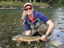 Cailey McCutcheon standing with waders in a river holding a fish