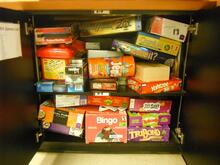 assortment of board games stacked in a cabinet