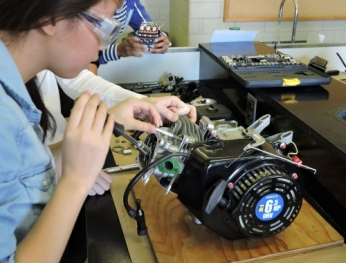 a female engineering student works on a motor