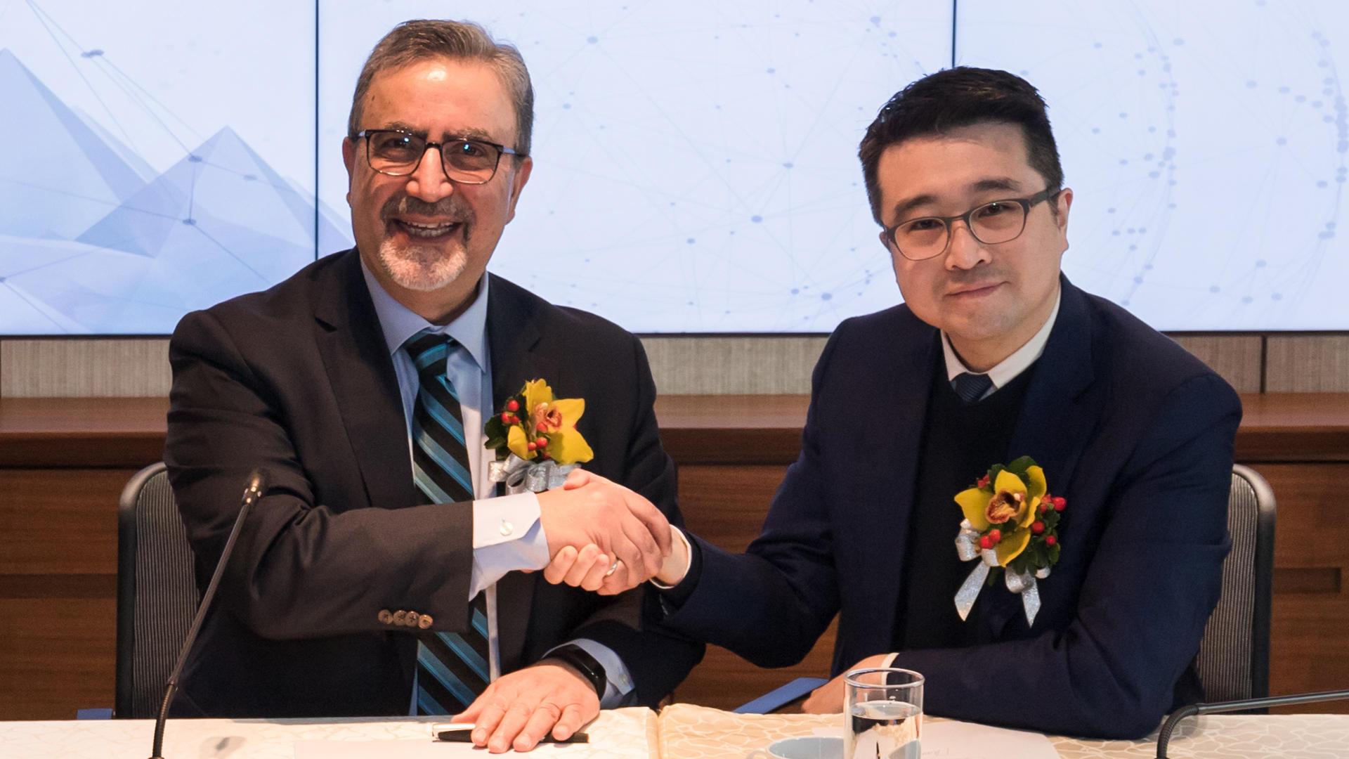 Feridun Hamdullahpur shakes hands with Calvin Choi