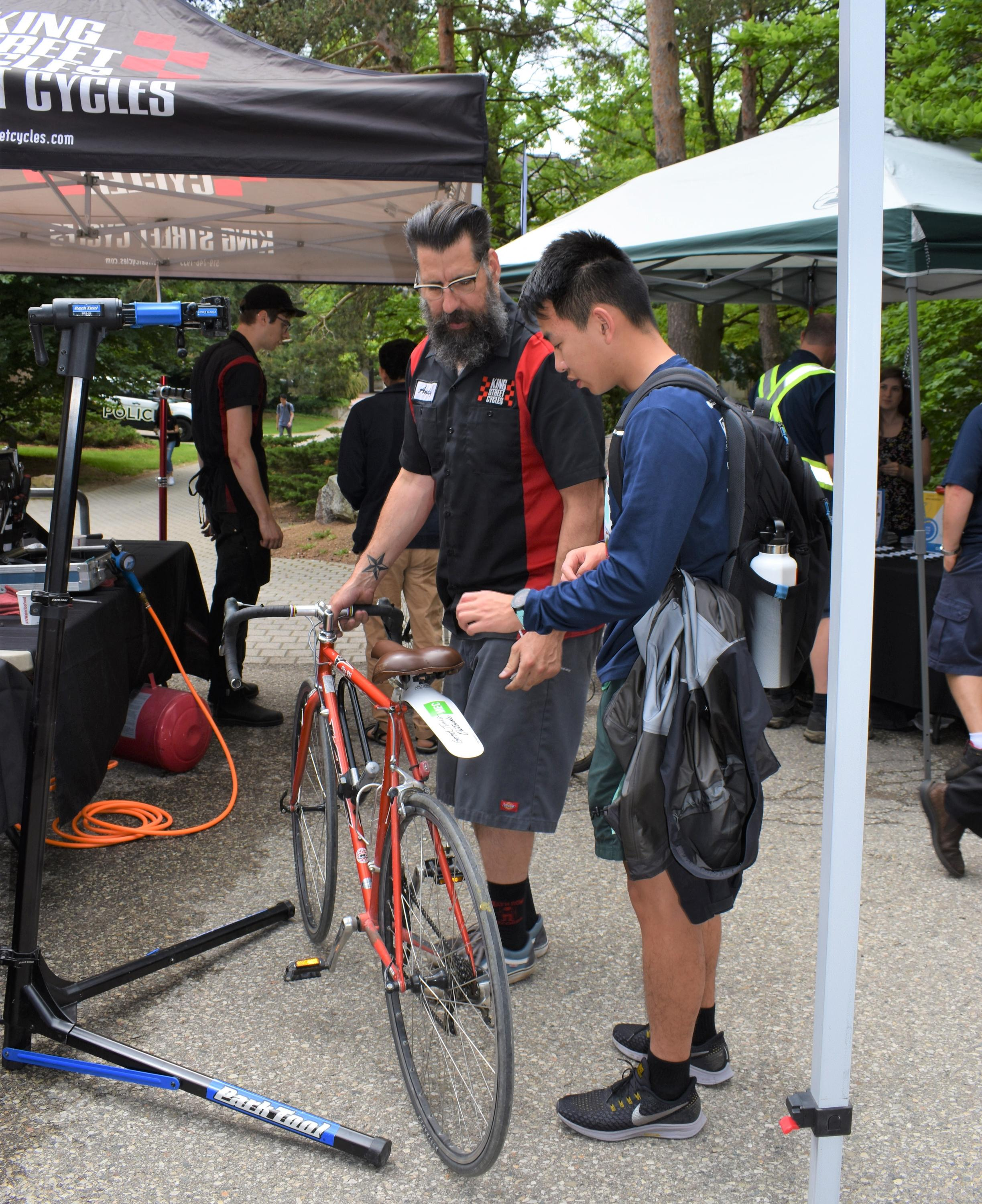 King Street Cycles mechanic fixing student bike as student watches