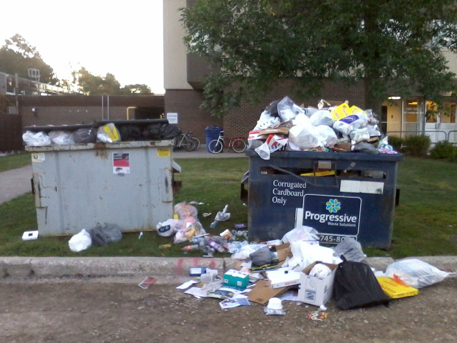 two overflowing dumpsters on campus