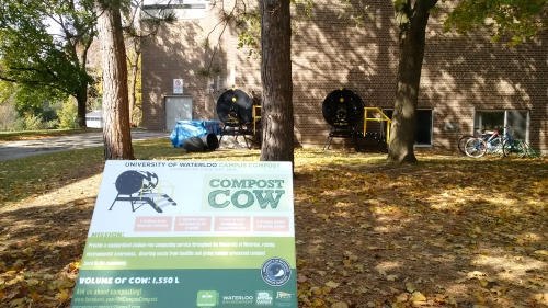 Campus compost sign with compost cows in background