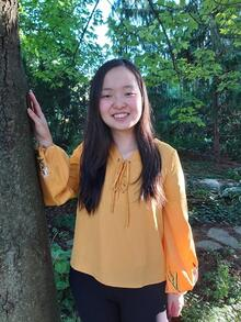 Maggie Chang standing next to tree