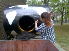 Student emptying composted material from compost tumbler