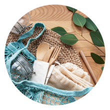 Reusable cloth bag with jar and reusable cutlery on a wood table with greenery