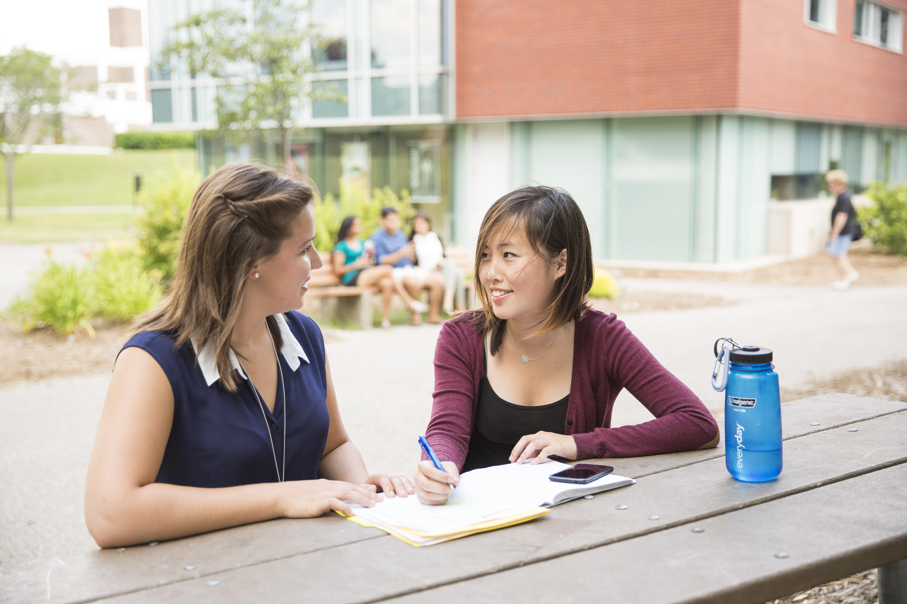 Two students at a picnic table in DP quad area