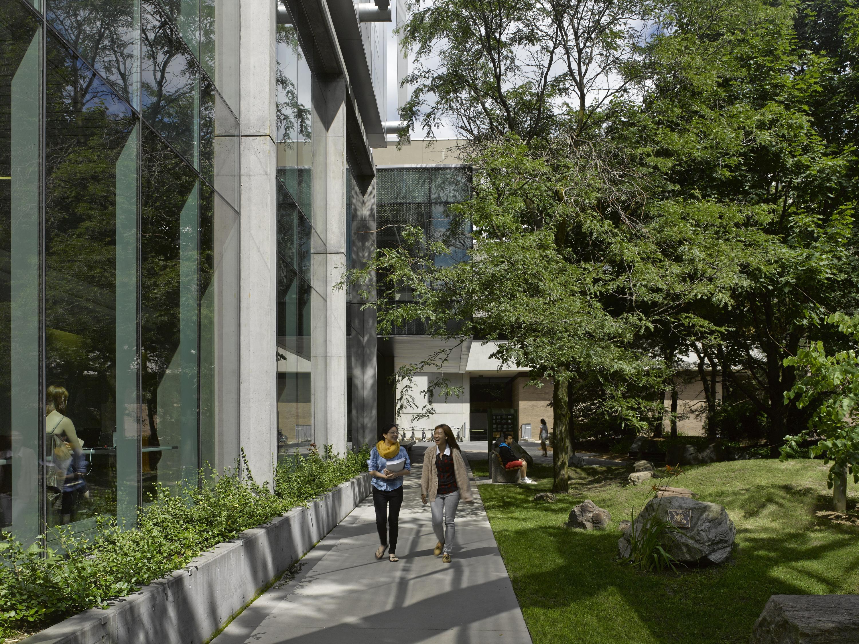 Two students walk alongside QNC building