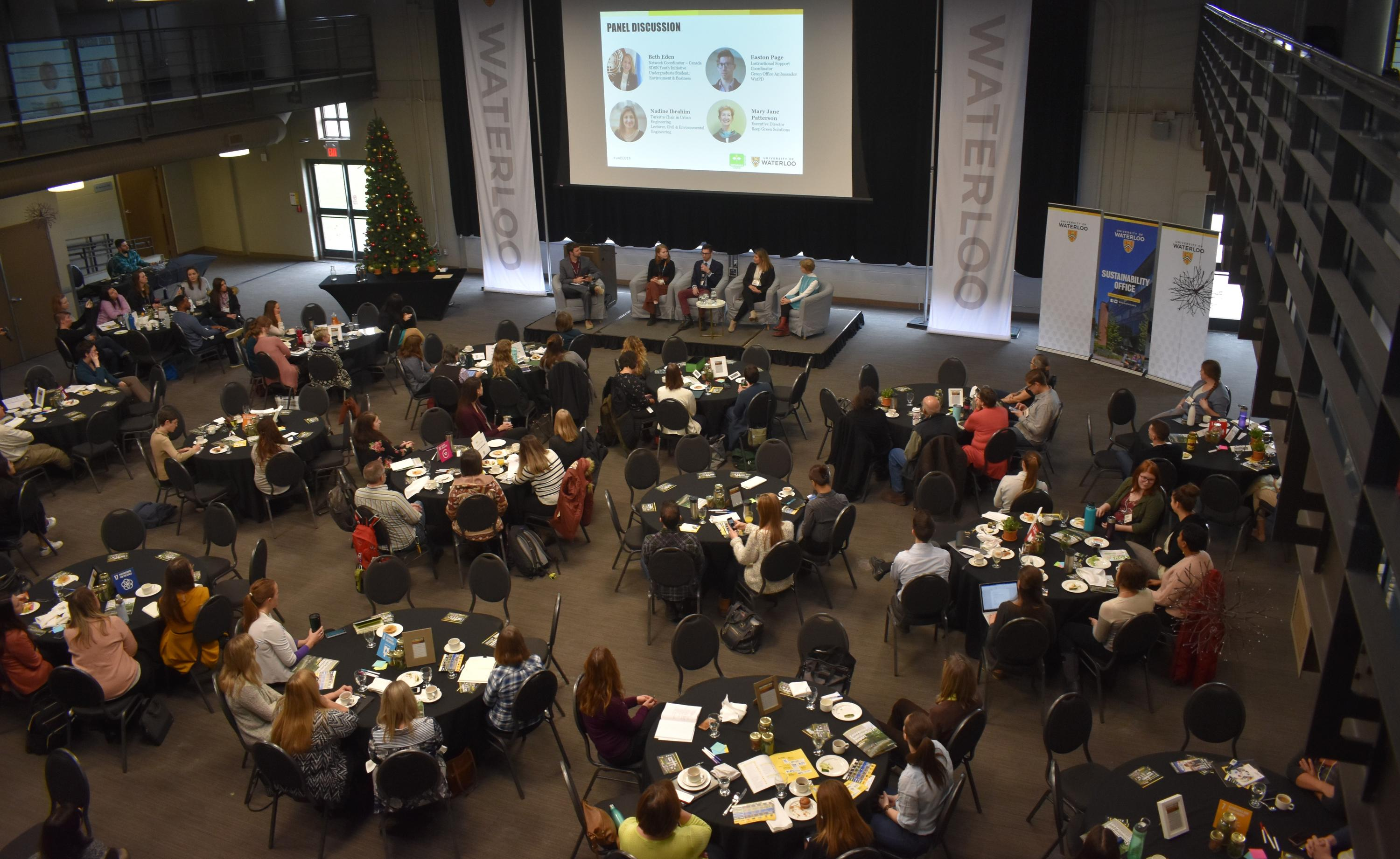 Aerial shot of Eco Summit event, with panel members on stage and participants at round tables in audience