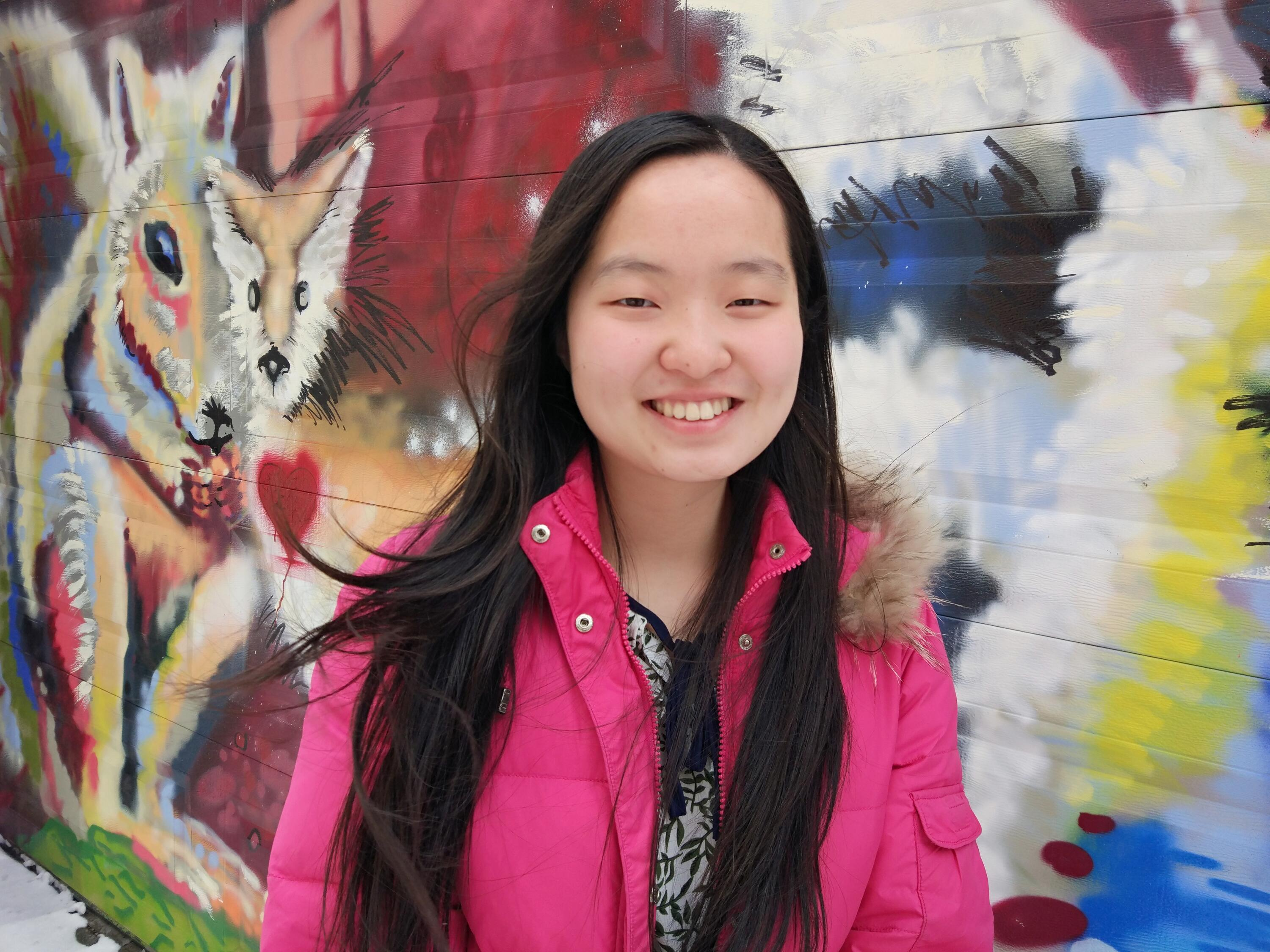 Maggie Chang standing in front of wall mural
