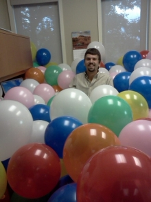 Jonathan Brubacher sits in a room full of balloons.