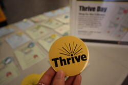 A hand holding a Thrive button in front of a table