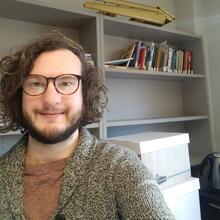 Thomas Littlewood wearing jacket with bookshelf background