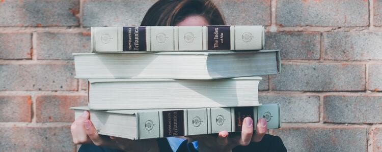 person holding a stack of books in front of their face
