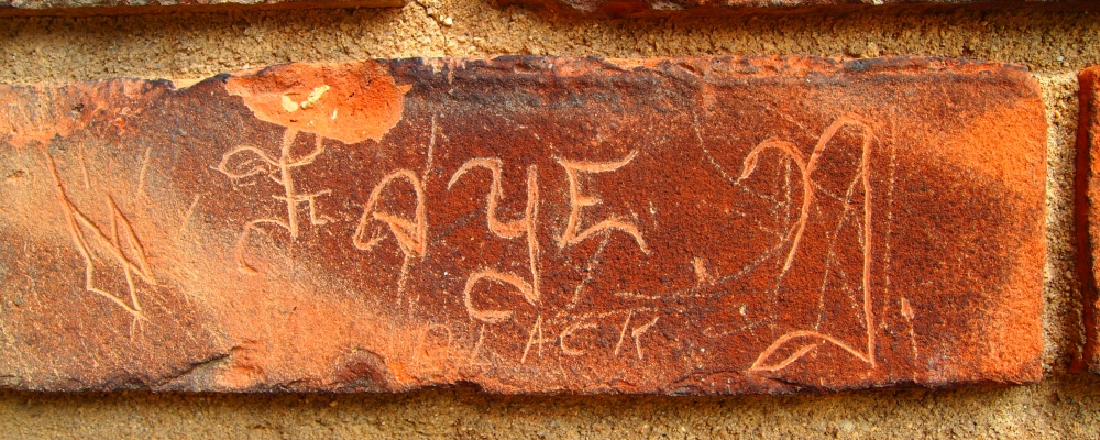 "the name ""Faye N."" carved in brick in wall"