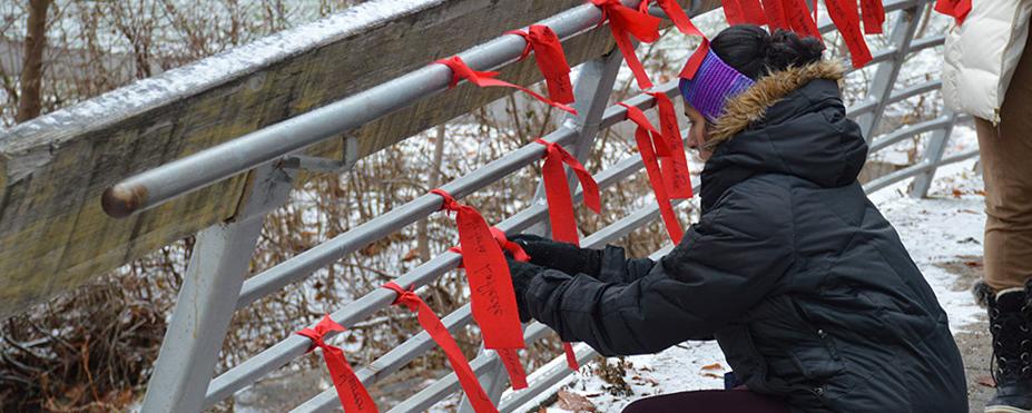 Woman tying red ribbons to bridge railing