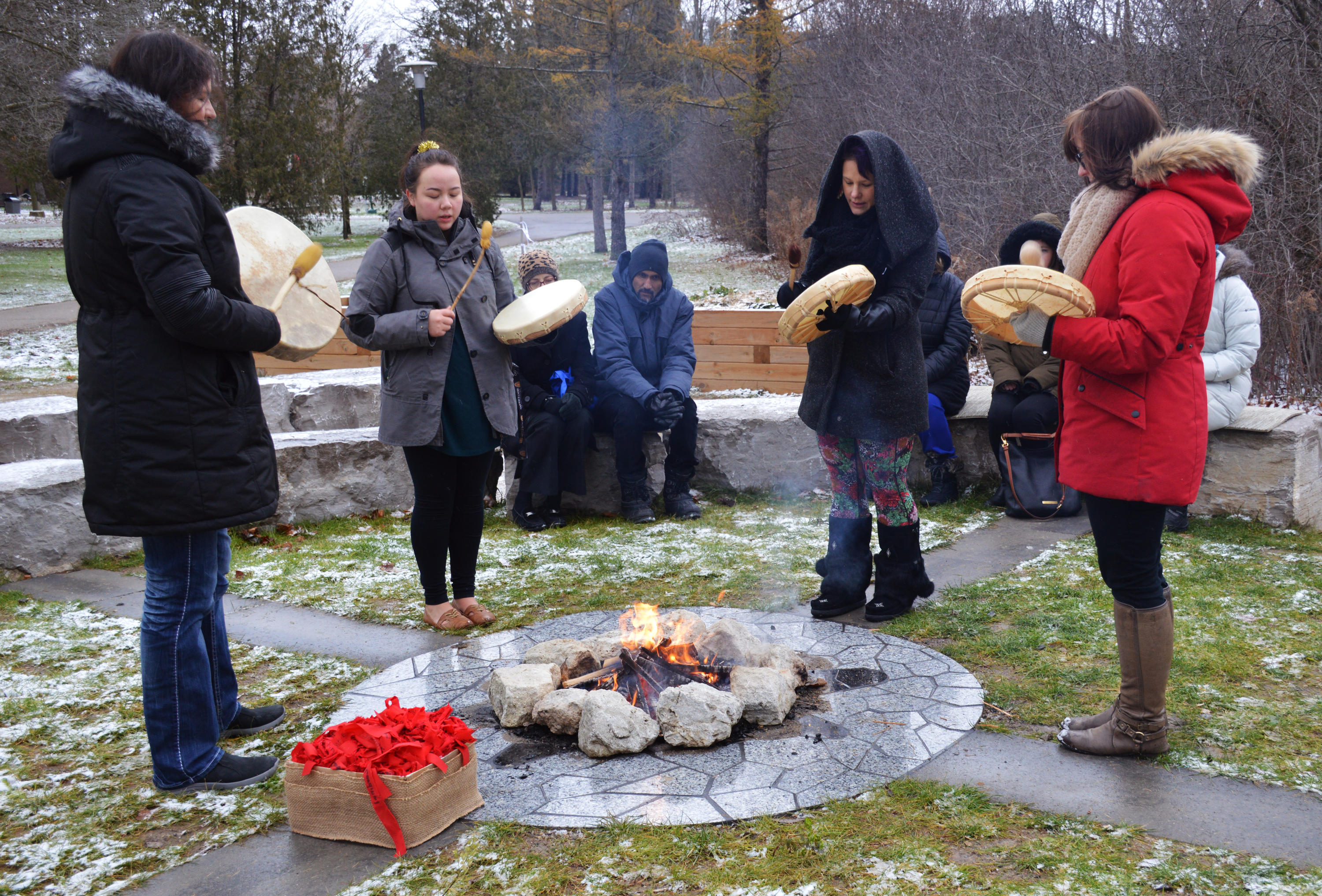 four women drumming and singing around fire