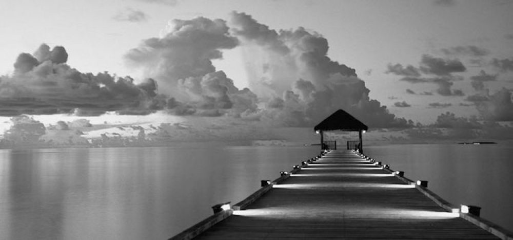 Illuminated dock leads out to distance on still waters with cloudy skies.