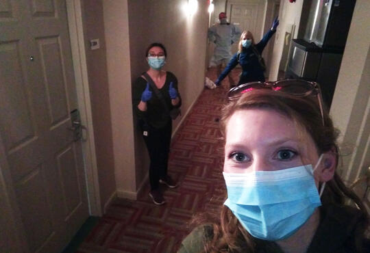 The team at Houe of Friendship ose in masks, 2 meters apart, in the hallway of one of their housing locations.