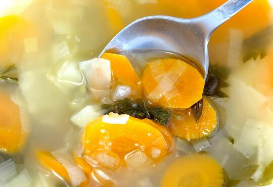 A close up of vegetable soup with a spoon